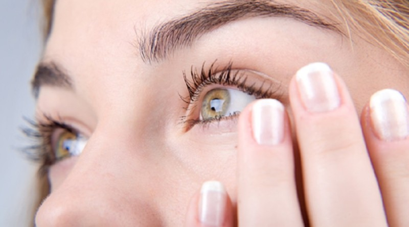 Opened green eyes and fingernails with french manicure close-up